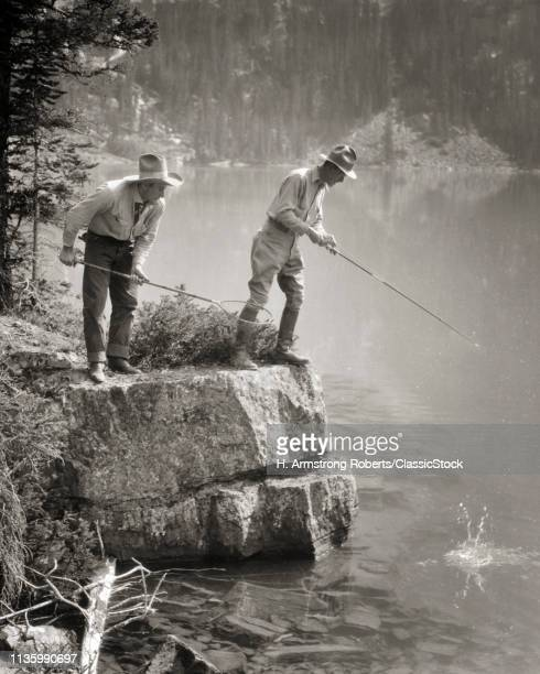 1920s TWO MEN STANDING ON ROCKY SHORE FISHING IN LAKE O'HARA BRITISH COLUMBIA CANADA