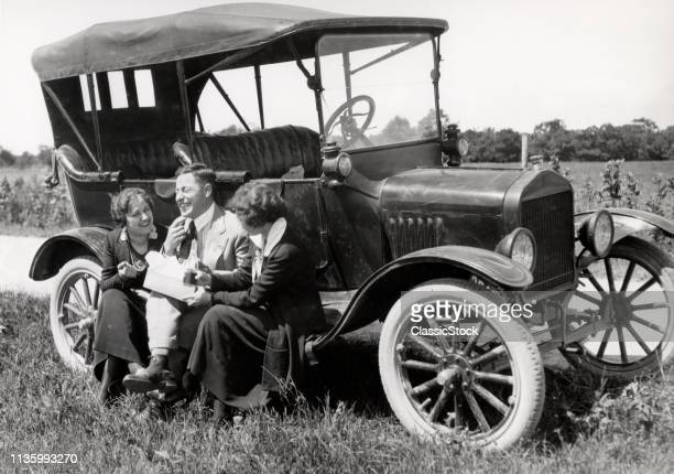 1920s TWO WOMEN & ONE MAN SITTING ON RUNNING BOARD OF MODEL T FORD EATING LUNCH TALKING & LAUGHING