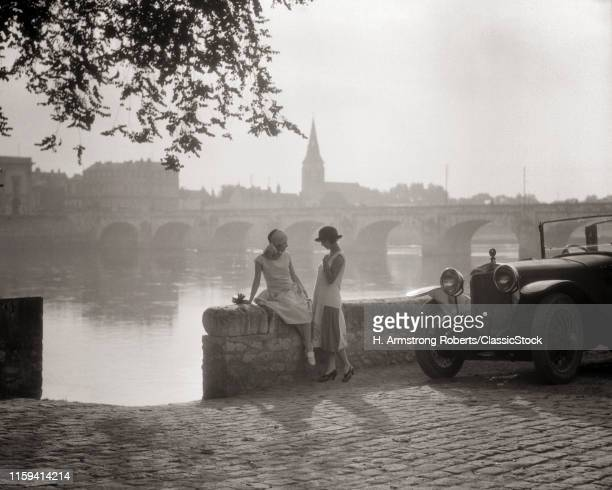 1920s TWO YOUNG WOMEN WITH ANTIQUE AUTOMOBILE SITTING STANDING TOGETHER TALKING BY STONE WALL LOIRE RIVER VALLEY FRANCE