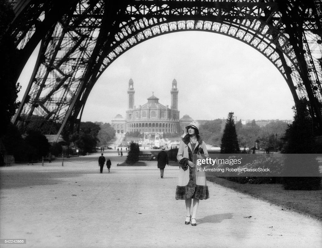 1920s WOMAN WALKING UNDER... : Nachrichtenfoto