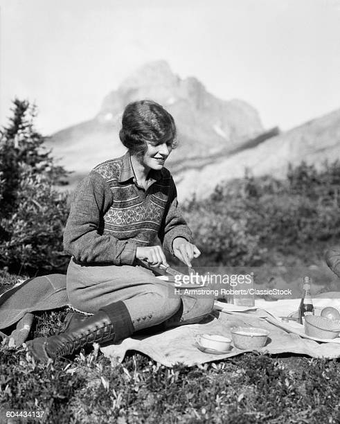 1920s WOMAN CAMPING EATING BREAKFAST OUTDOORS SITTING ON GRASS MOUNTAINS IN BACKGROUND BAKER LAKE ALBERTA CANADA
