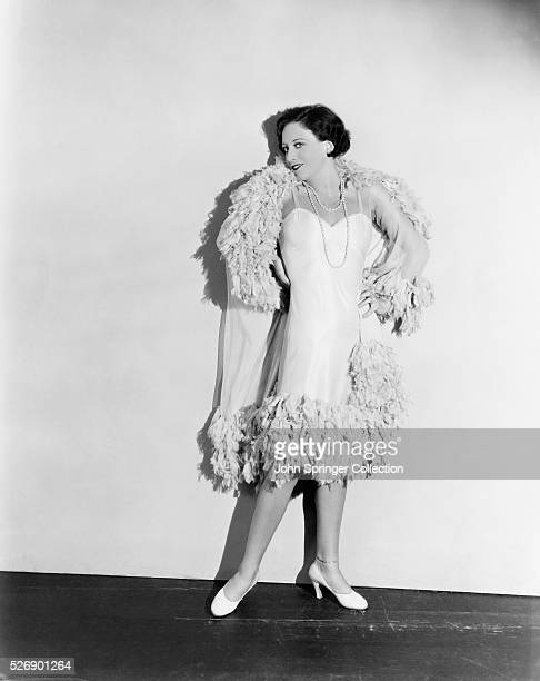 Young Joan Crawford stands posed in a dress and jacket with unusual trim before a white backdrop Crawford won an Oscar for her lead performance in...