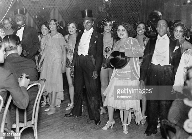 Picture shows men and women entertainers at Small's Paradise Clubin Harlem Photo shows man in tuxedo and top hat in center