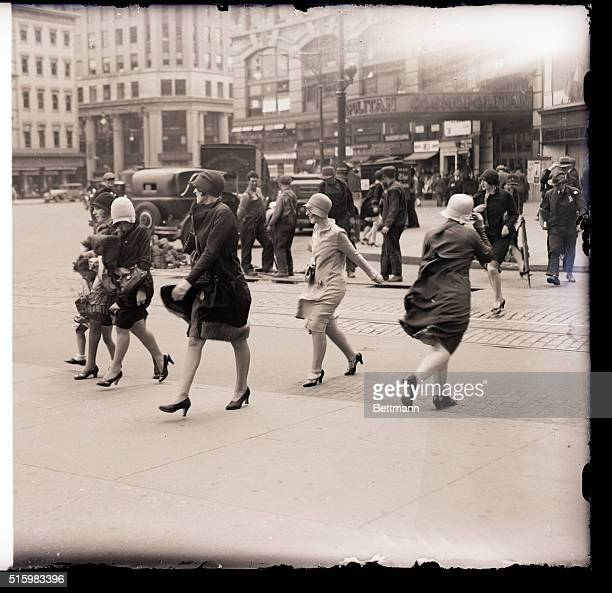 Photo shows a windy scene at Columbus Circle in New York City People are shown walking on the street being provided with extra motivation by the wind