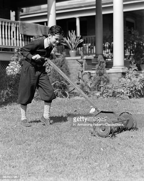 1930s 1920s BOY PUSHING LAWN MOWER WEARING KNICKERS CUTTING THE GRASS