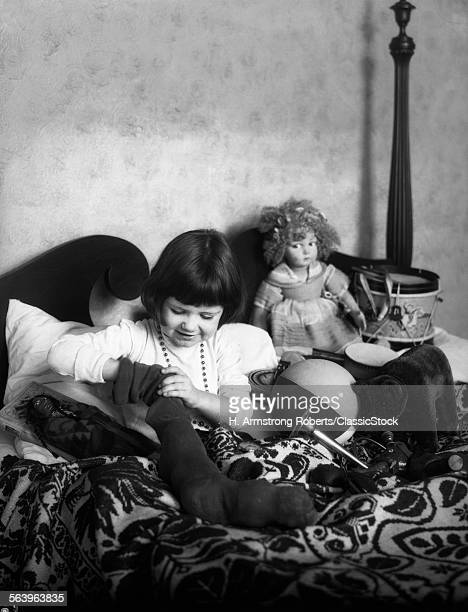 1930s 1920s GIRL IN BED WITH STOCKING FULL OF TOYS DOLLS STUFFED ANIMALS DRUM