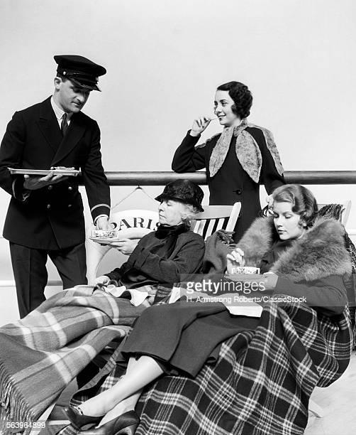 1930s 1920s THREE WOMEN BEING SERVED TEA BY A STEWARD ON BOARD AN OCEAN LINER CROSSING THE ATLANTIC OCEAN