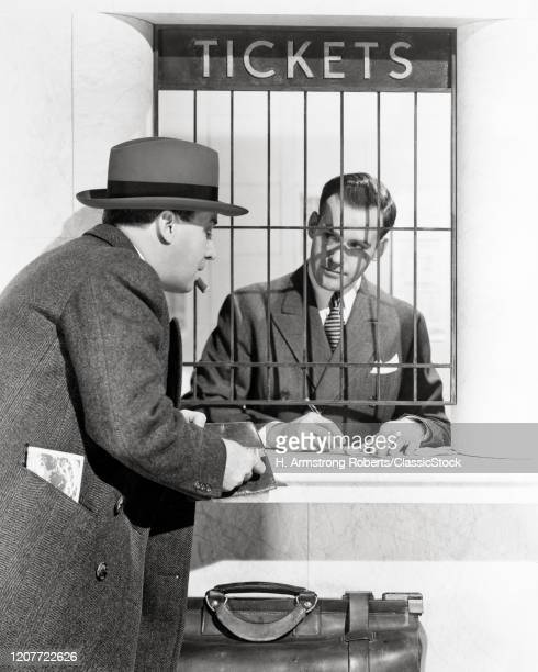 1930s 1940s 1950s man buying ticket at window in bus or railroad train station