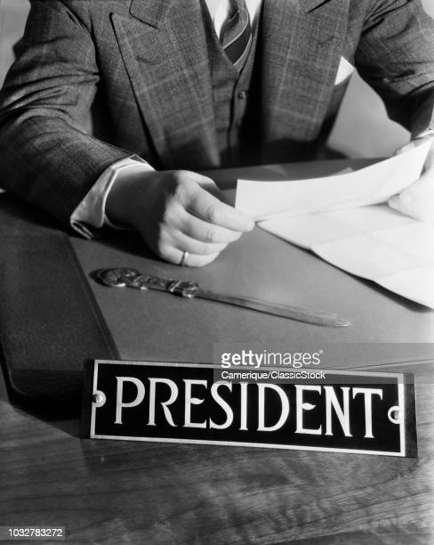 1930s 1940s 1950s MAN SITTING AT DESK READING LETTER WITH SIGN PRESIDENT
