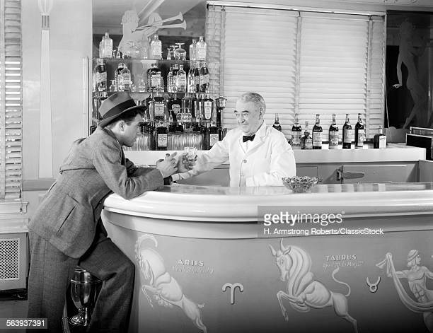 1930s 1940s 1950s MAN LEANING ON BAR ORDERING ANOTHER ALCOHOLIC DRINK FROM BARTENDER IN ART DECO STYLE COCKTAIL LOUNGE