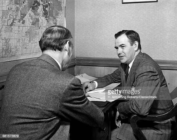 1930s 1940s 2 MEN AT DESK MEETING INTERVIEWING ONE SEEN FROM BACK MAP ON WALL