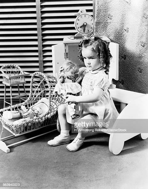 1930s 1940s 3 YEAR OLD GIRL SITTING HOLDING BABY DOLL BESIDE TOY CRADLE TOY HIGH CHAIR & TOY CLOCK