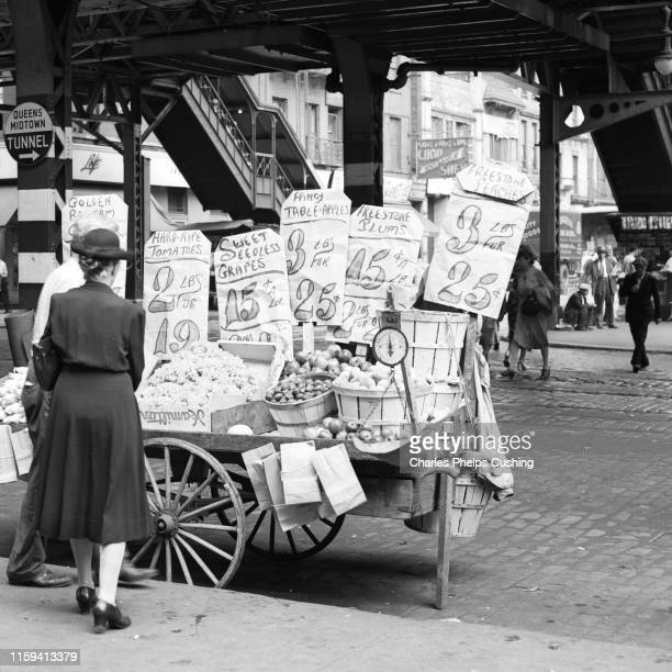 1930s 1940s 59TH STREET THIRD AVENUE UNDER EL STATION WOMAN SHOPPING FOR VEGETABLES AT STREET VENDOR PUSH CART NEW YORK CITY USA
