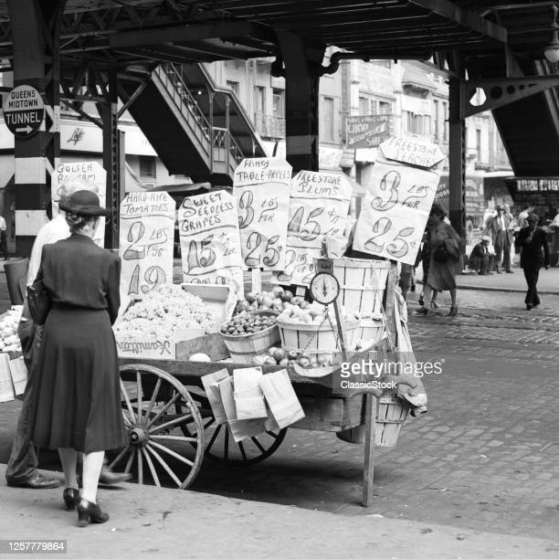 1930s 1940s 59th Street Third Avenue Under Station Woman Shopping For Vegetables At Street Vendor Push Cart New York City USA