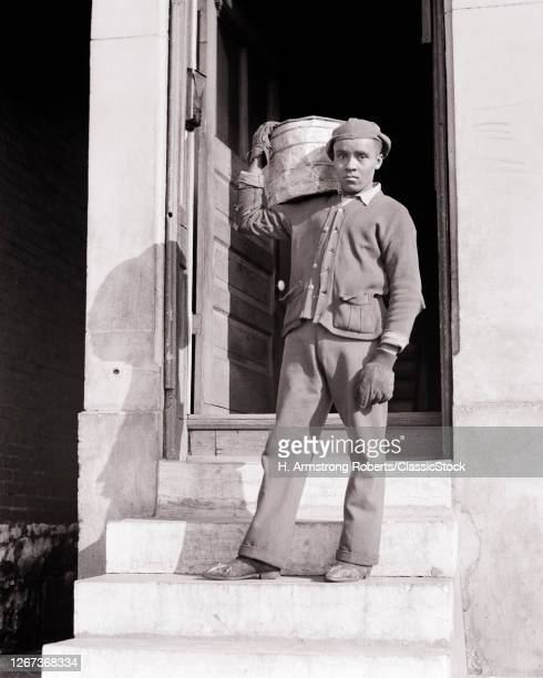 1930s 1940s African-American Man Worker Carrying Removing Coal Furnace Heater Heavy Metal Ash Can From City Building Back Door