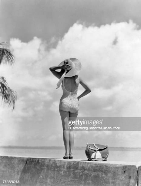 1930s 1940s ANONYMOUS WOMAN BACK VIEW FULL LENGTH STANDING ON TROPICAL BEACH WALL HOLDING ON TO HER AT IN BREEZE