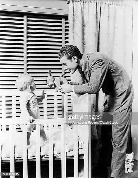 1930s 1940s BABY STANDING IN CRIB IN FRONT OF WINDOW WITH VENETIAN BLINDS FATHER HANDING BABY A TOY DOG STUFFED ANIMAL NURSERY