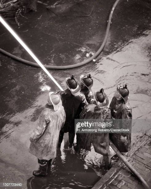 1930s 1940s back view of four fireman manning a hose standing next to them on this wet city street is their captain.