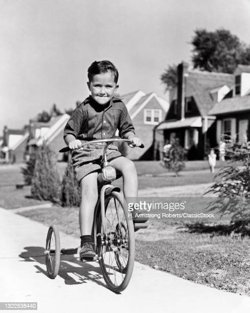 1930s 1940s Boy Riding Tricycle Bike On Suburban Sidewalk Smiling Happy Determined Facial Expression Looking At Camera .