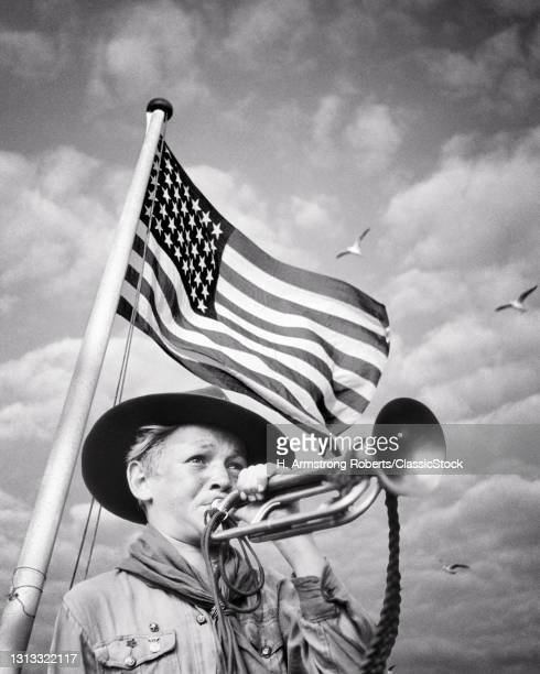 1930s 1940s Boy Scout In Uniform Blowing A Bugle In Front Of A 48 Star American Flag .