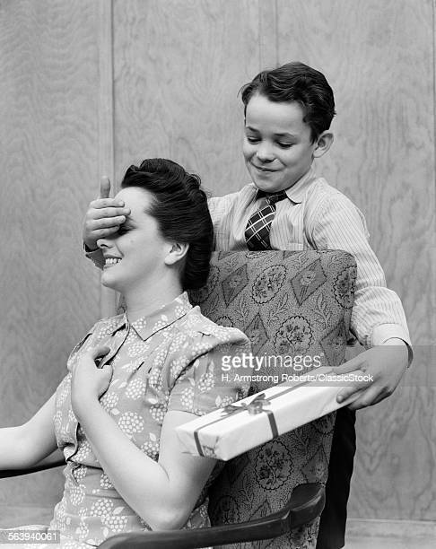 1930s 1940s BOY SON SURPRISING WOMAN MOTHER WITH GIFT WRAPPED PRESENT