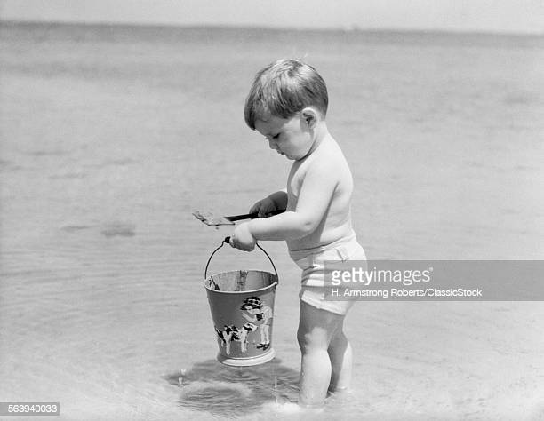 1930s 1940s BOY TODDLER ON BEACH WITH SHOVEL AND SAND PAIL BUCKET SUMMER FUN SEASHORE PLAY