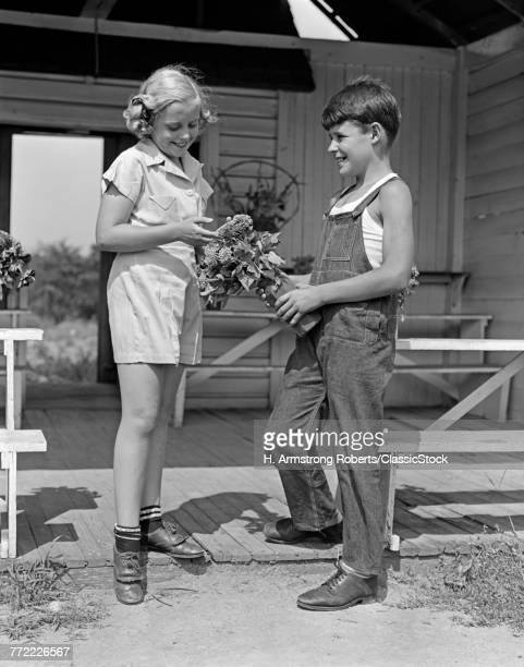 1930s 1940s BOY WEARING OVERALLS GIVING GIRL BOUQUET OF FLOWERS AT FARM STAND
