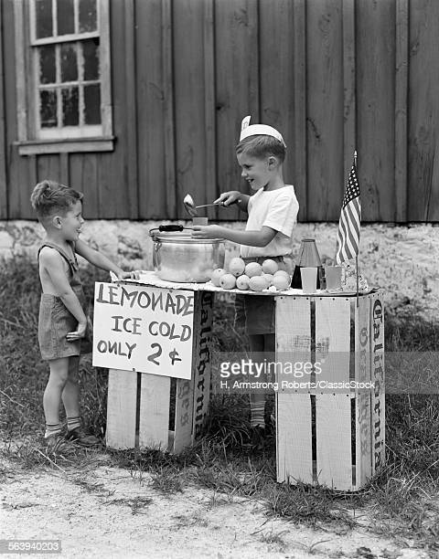 1930s 1940s BOY WITH LEMONADE STAND SELLING TO LITTLE BOY IN SHORT PANTS