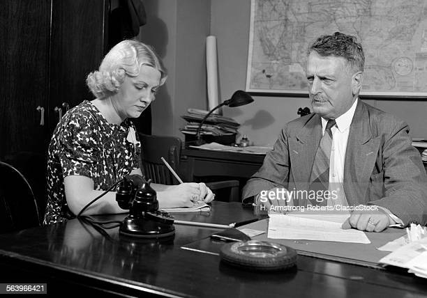 1930s 1940s BUSINESSMAN SITTING AT DESK GOING OVER PAPERWORK WITH SECRETARY TAKING DICTATION MAN WOMAN OFFICE INDOOR