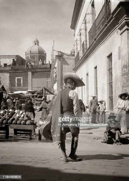 1930s 1940s BUSY GUADALUPE MARKET IN MEXICO CITY ANONYMOUS BOWLEGGED MAN WALKING IN FOREGROUND WEARING SERAPE AND SOMBRERO