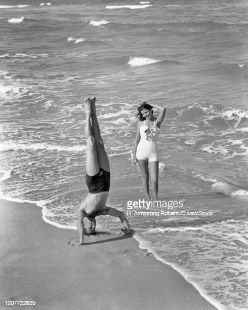 1930s 1940s couple at beach woman watching man do handstand in sand at edge of ocean surf.