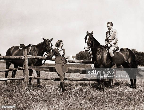 1930s 1940s COUPLE IN RIDING GEAR MAN RIDING HORSE WOMAN STANDING BY WOODEN FENCE