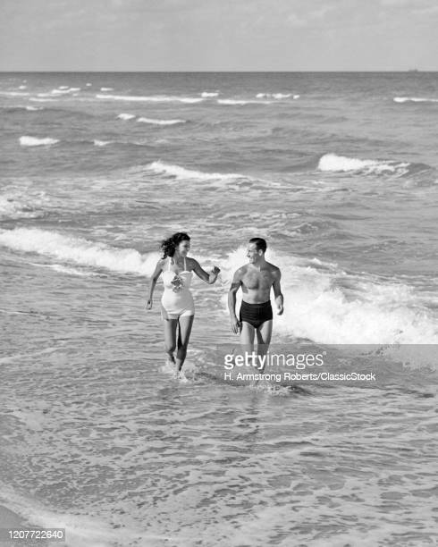 1930s 1940s couple wearing bathing suits jogging running talking together on bright warm sunlit seashore ocean beach sand