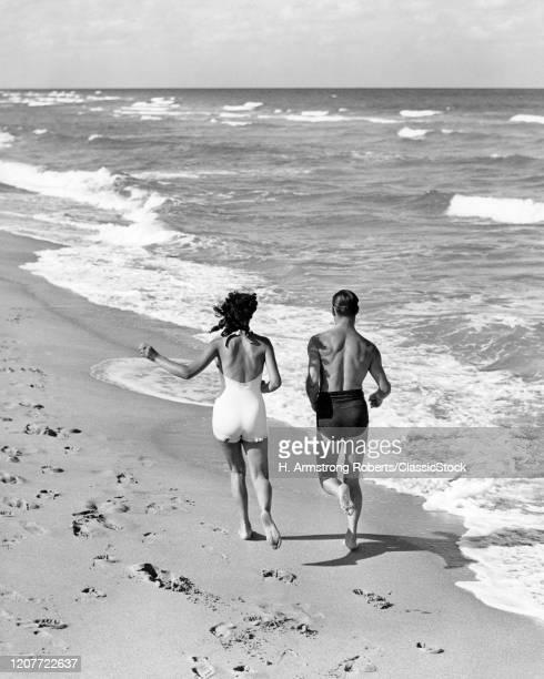 1930s 1940s couple wearing bathing suits jogging running together at edge of surf on ocean beach.