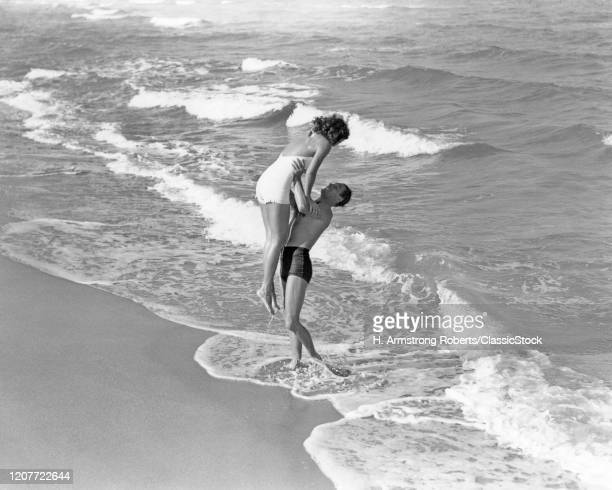 1930s 1940s couple wearing bathing suits man lifting woman playing together in ocean surf at beach Florida USA