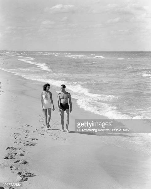 1930s 1940s couple wearing bathing suits walking talking together on bright warm sunlit seashore ocean beach sand