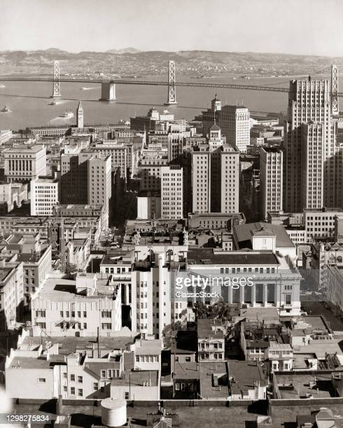 1930s 1940s Downtown City Buildings With Western Section Of Oakland Bay Bridge In Background San Francisco California USA.