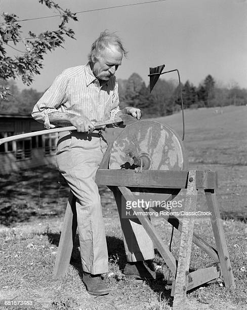 1930s 1940s ELDERLY MAN SEATED AT PEDAL DRIVEN GRINDSTONE OUTDOORS SHARPEN LONG HANDLE AXE