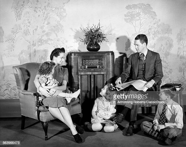 1930s 1940s FAMILY MAN FATHER WOMAN MOTHER BOY SON TWO GIRLS DAUGHTERS SITTING TOGETHER LISTENING TO RADIO