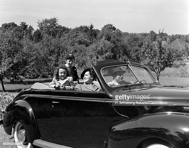 1930s 1940s FAMILY MOTHER FATHER DAUGHTER SON IN CONVERTIBLE CAR ON SUNDAY DRIVE IN COUNTRY
