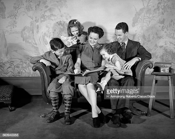 1930s 1940s FAMILY SITTING ON COUCH LOOKING READING BOOK TOGETHER