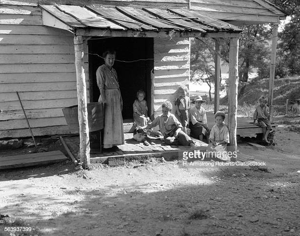 1930s 1940s FARM WOMAN WITH SIX CHILDREN ON PORCH OF CLAP BOARD FARM HOUSE