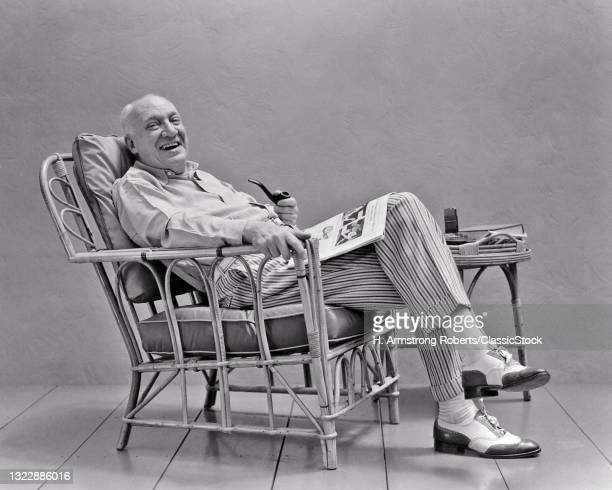 1930s 1940s Fashionably Dressed Man Sitting In Rattan Chair Smoking A Pipe Reading Newspaper Magazine Smiling Looking At Camera.