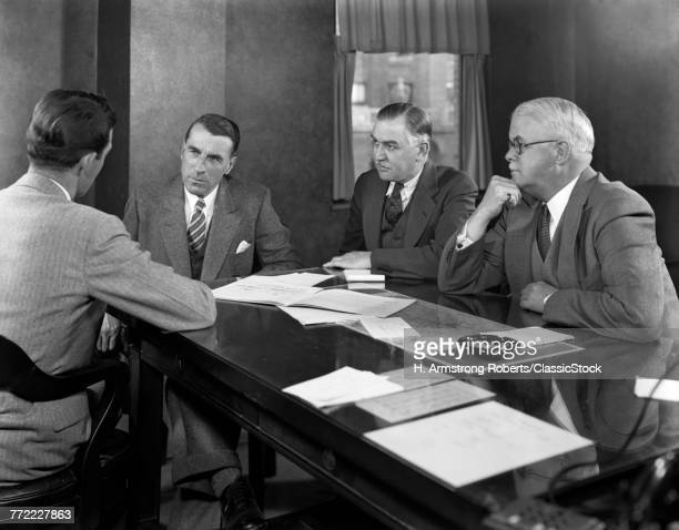 1930s 1940s FOUR BUSINESSMEN SITTING AT TABLE IN OFFICE CONFERENCE