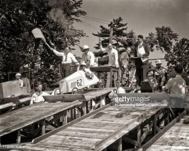1930s 1940s GROUP OF FATHERS AND SONS AT SOAP BOX DERBY RACE CONTEST STARTING LINE