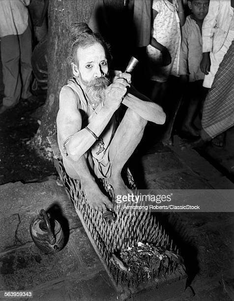 1930s 1940s HINDU HOLY MAN FAKIR SITTING ON BED OF SPIKES AND NAILS BOMBAY INDIA