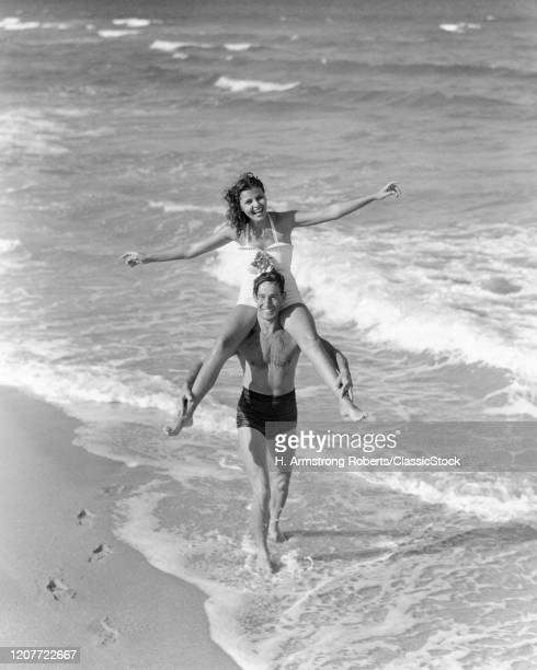 1930s 1940s laughing smiling vacation couple wearing bathing suits playing in ocean surf at beach man carrying woman Florida USA