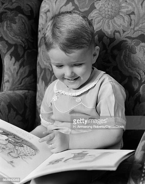 1930s 1940s LITTLE BOY SITTING ON CHAIR READING PICTURE BOOK
