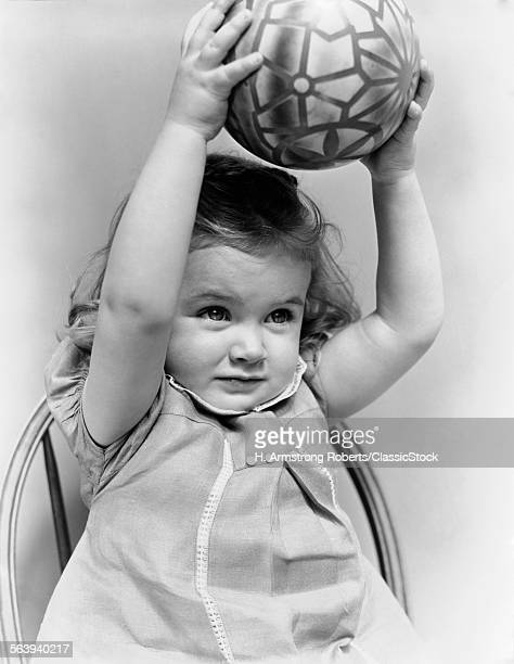 1930s 1940s LITTLE GIRL TODDLER HOLDING TOY BALL ABOVE HER HEAD WITH BOTH ARMS