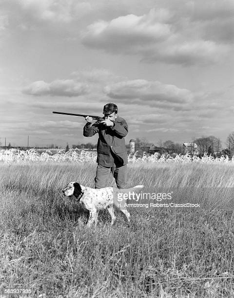 1930s 1940s MAN BIRD HUNTING IN FIELD WITH DOG AIMING SHOTGUN